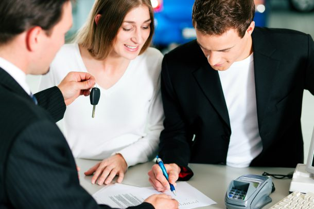 Sales situation in a car dealership, the young couple is signing the sales contract and gets the key for the new car, Image: Kzenon/Bigstock.com