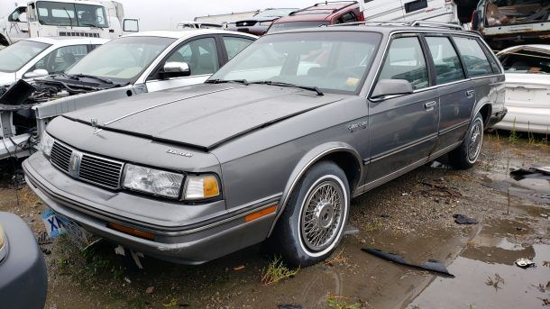 1988 Oldsmobile Cutlass Cruiser wagon in North Dakota junkyard, LH front view - ©2019 Murilee Martin - The Truth About Cars